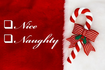 46001382 - naughty or nice,  a plush red stocking with a candy cane and words nice and naughty