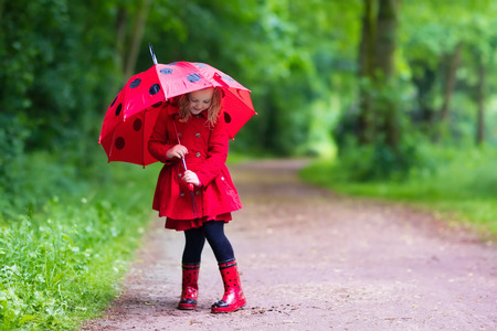 Little girl playing in rainy summer park.
