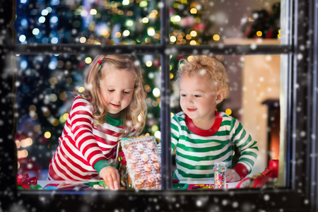Kids playing with ginger bread under Christmas tree.