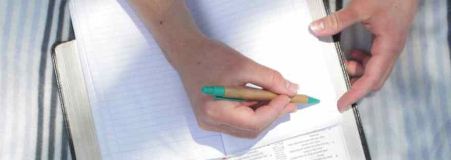 One of the secrets of setting your goals is to write them down. Image of a hand with pen writing down notes.