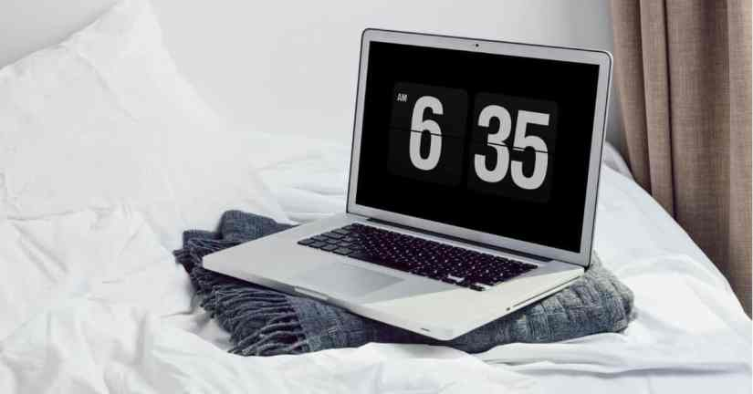 Change your routine to get up earlier to get more of your goals accomplished. Image of a clock on laptop on top of a folded blue blanket on top of a bed with white bedding.