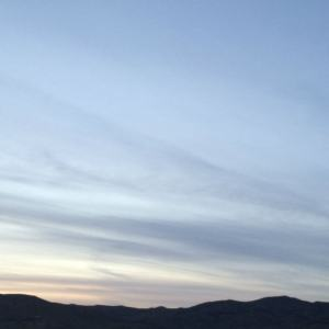 Blessed Catholic Mom: Conquering feelings of overwhelm and nurturing faith to live a more joyful life. Image of a blue and purple sunset over foothills.