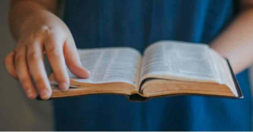 Learn form God to be greatful. Image of two hands holding Bible and about to turn the page.