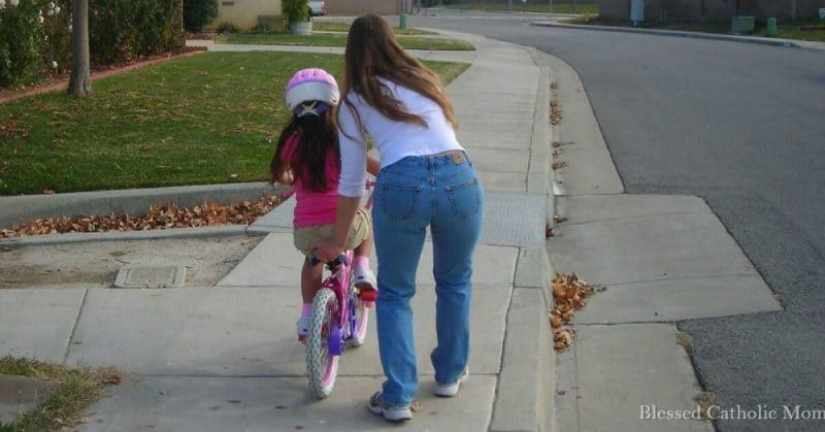 Am I trying now to be a saint? Am I putting this goal on my to-do list? I can live my vocation faithfully. I can fully rely on God to help me. Image of a mom helping her daughter learn to ride a bike without training wheels. Blessed Catholic Mom logo in corner.