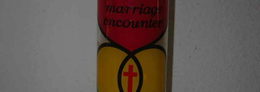 Give the gift to your marriage of a Marriage Encounter Weekend. Image of the Marriage Encounter logo on a candle: a red heart above two gold intertwined rings that have a red cross in the section where the rings intersect.