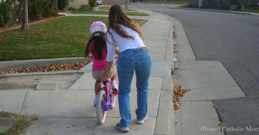 I can work each day as a mom to set a great example for our kids. Being a great mom does not equal being a perfect mom. I can rely on God's help. Image of a mom helping her daughter to learn to ride a bike without training wheels. Blessed Catholic Mom logo on image in right corner.
