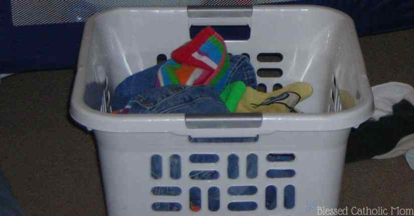 Here is a simple solution to our family's laundry dilemma: kids can do their own laundry. When we work as a family, we share the work load. Image of a white basket full of laundry. Blessed Catholic Mom logo on image.