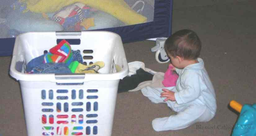 Here is a simple solution to our family's laundry dilemma: kids can do their own laundry. When we work as a family, we share the work load. Image of a white basket full of laundry and a toddler boy sitting beside it with clothes on the floor by him.