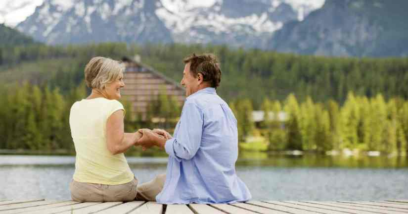 Do you and your spouse yearn to grow closer as a couple, yet think you'll never be close again? You can grow closer. It is possible and worth the effort! Take the time to really listen to each other. Image of a couple sitting on a dock over the water holding hands, smiling, and looking into each others' eyes.
