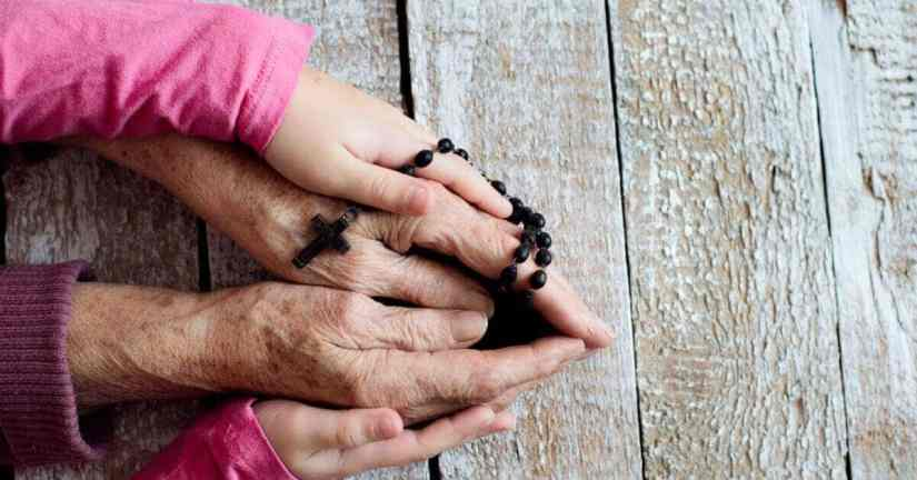 Do you want to start a family Rosary group? just follow these four simple steps. It is a fun and meaningful way for your family to pray the Rosary together. Image of two sets of hands together holding a Rosary.