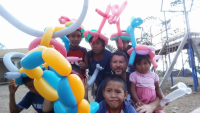 A teacher in a group of children and their baloon animals