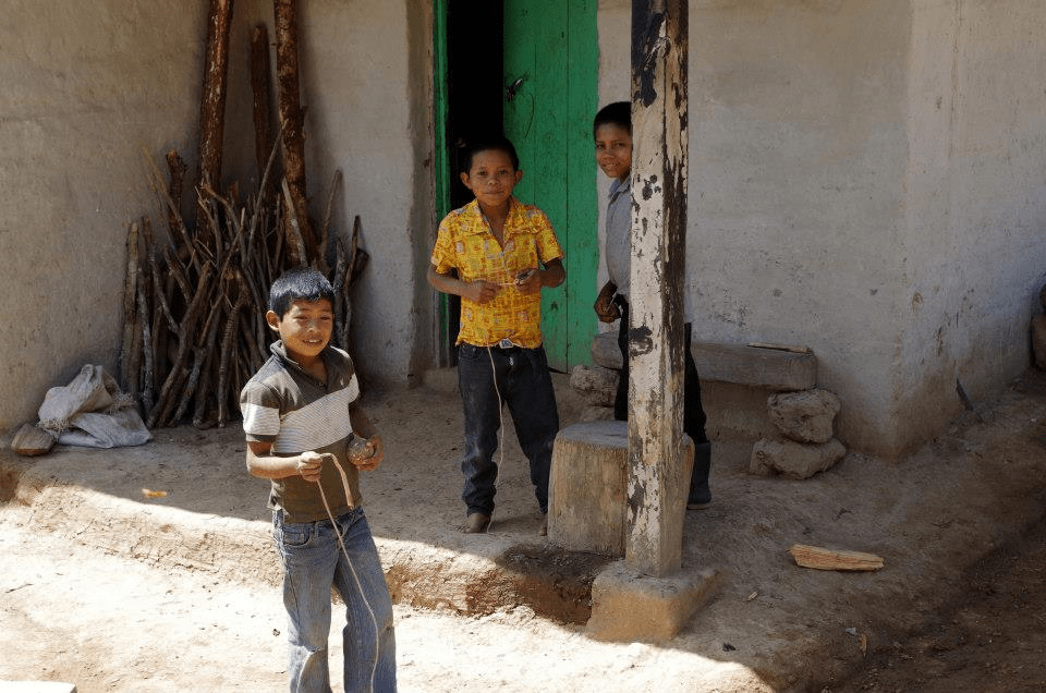 3 young men stand outside their house made of adobe in Honduras