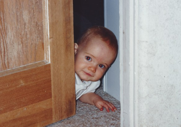baby crawling and peeking out behind door.