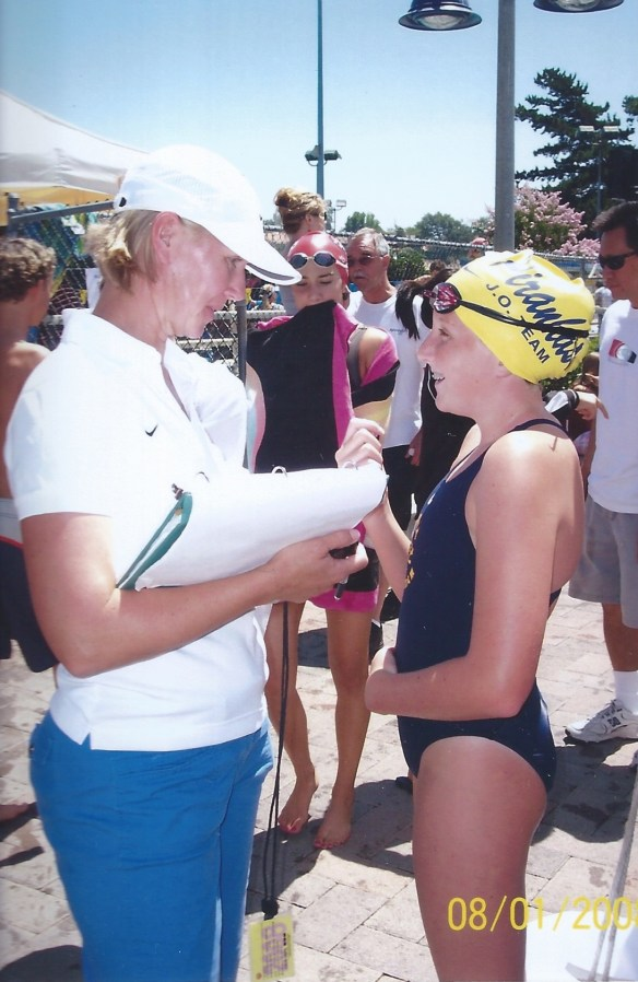 swim coach with young swimmer