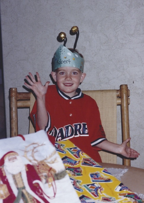 boy wearing birthday crown and bug antennae