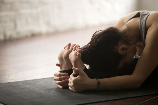 75178717 - young sporty yogi woman practicing yoga concept, sitting in paschimottanasana exercise, seated forward bend pose, working out on black mat, studio floor background, legs and hands close up