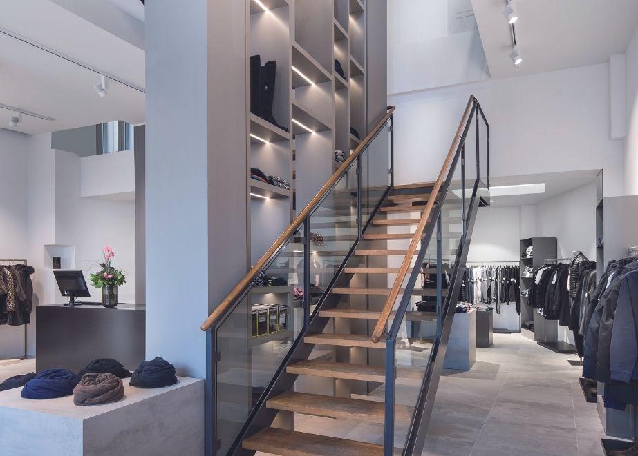 Eine mittig angeordnete, offene Holz-Stahltreppe bei Brauneis Fashion in Frankfurt/Main windet sich geradlinig um ein offenes Regal und dient so als Raumtrenner.