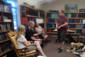 Nik is standing with a Focus 14 refreshable Braille display hanging from a strap around his neck. Three parents are watching an iPhone, held by one parent as Nik controls it with the Braille display. Nik's guide dog, Sully rests in the background. They are sitting inside in the library at Hull Park.