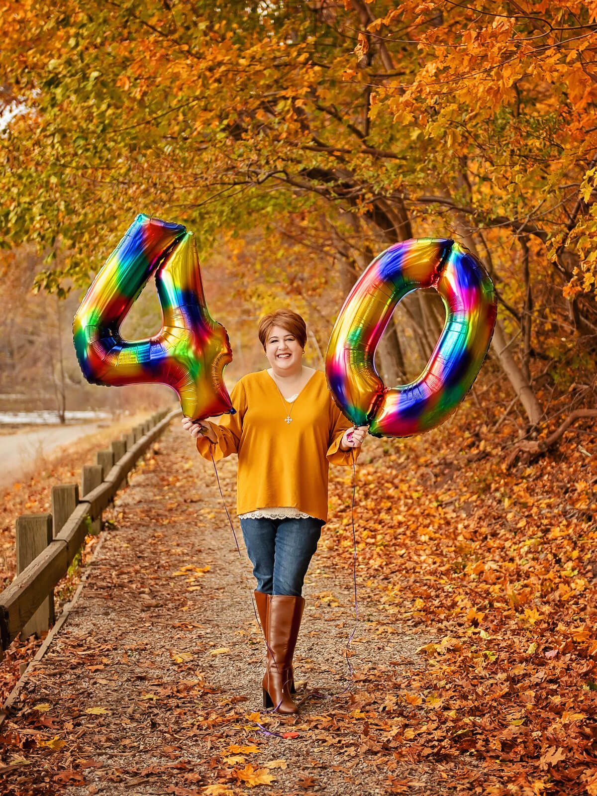 """Holly in marigold sweater, jeans, and brown boots on a fall day holding a multi-colored """"4"""" and """"0"""" balloon."""