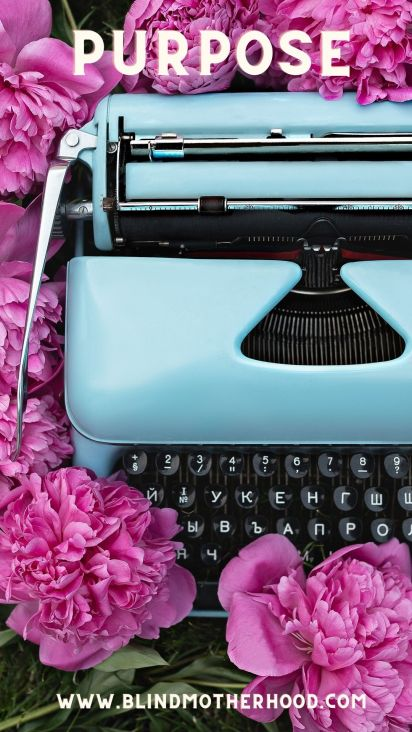 Blue typewriter against purple flowers.