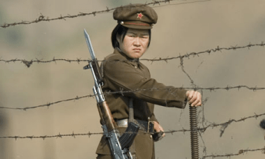 North Korean soldier mans the border with South Korea where nearly 25 million people are held by dictator Kim Jong-Un living in abject poverty