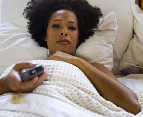 black woman-in-bed-watching-TV