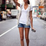 Supermodel Joan Smalls rocks her white tee shirt with an open vest and cut offs.
