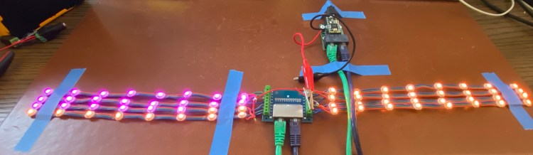 Teensy 3.2 mounted on an OctoWS2811 adapter, with two CAT-6 cables connecting it to a small dual RJ-45 breakout board, which is wired to 8 strips of 8 WS2812b LEDs.