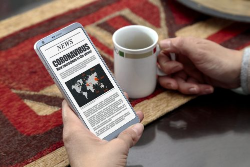 Coronavirus News. Woman with smartphone in her hands. Online newspaper page in the the screen.