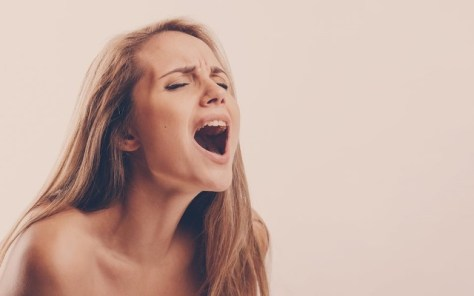 Blonde woman making intense orgasm face over light brown background