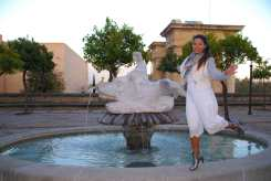 """Posing near a fountain, on the left side you can see the """"Puerta del Puente"""" or known in Cordoba as the """"Arco de Triunfo."""""""