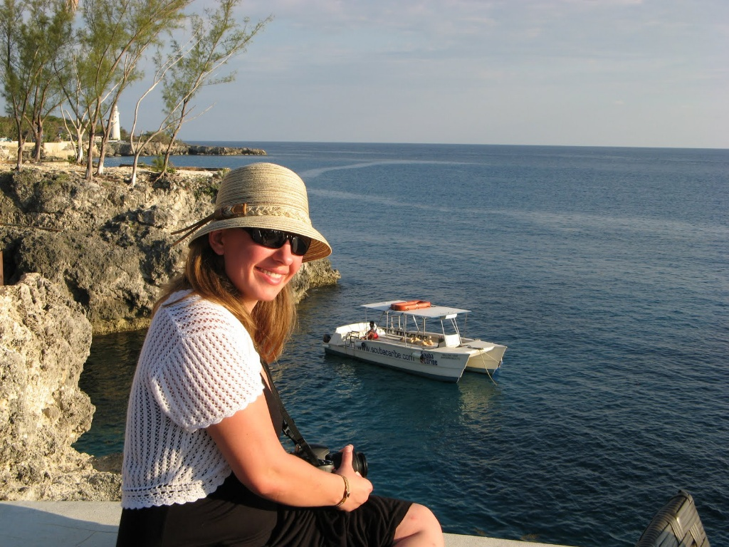 This is me, wearing a tan hat with a small brim, sunglasses, black dress, and white short-sleeved shrug. I'm sitting on a rock, overlooking the ocean and there is a boat in the distance. It was taken at Rick's Cafe in Negril, Jamaica.
