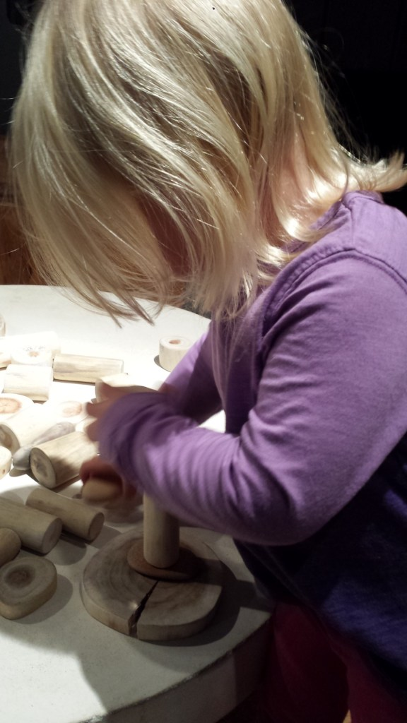 Child playing with wooden pieces to make a sculpture of sorts.