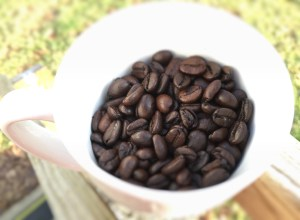 A picture of coffee beans in a white coffee mug.