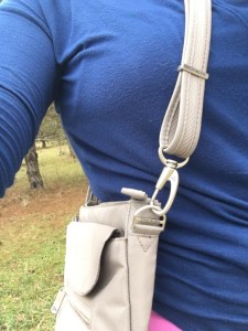 A torso in a blue shirt, modeling a travelon anti-theft purse.