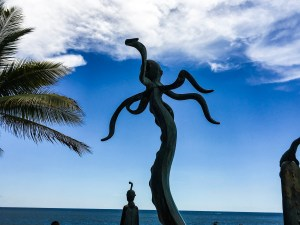 A statue of an octopus raised up on an artistic pole of sorts