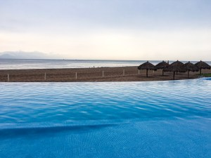 Pictured an infinity pool where it looks like the pool continues into the beach and ocean.