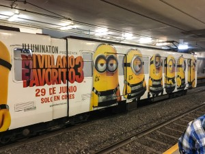 a subway train car is decked out with an advertisement for Despicable Me 3 in Spanish, with giant minions painted on.