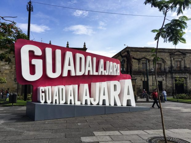 The Guadalajara city sign. White letters on a red background.