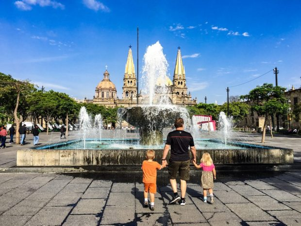 A fatherholding hands with two children, facing a fountain. There is a church and the guadalajara sign in the far background.