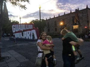 A mom smiling at the camera, holding a little girl who isn't looking at the camera, while the dad and son are wiggling and also not looking at the camera. They are standing in front of a red and white sign that says Guadalajara.