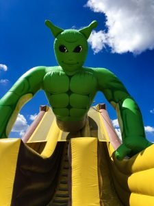 A giant inflatable slide with a green genie on top who resembles Shrek.