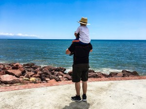 A father with his son sitting on his shoulders, staring out at the Pacific Ocean. Mom traveler, don't give up!