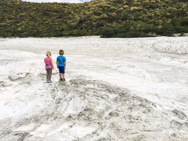 Two blonde children, the first wearing pink and the second blue, stand out against the white floor of a crater. You never know where in the world you may end up living!