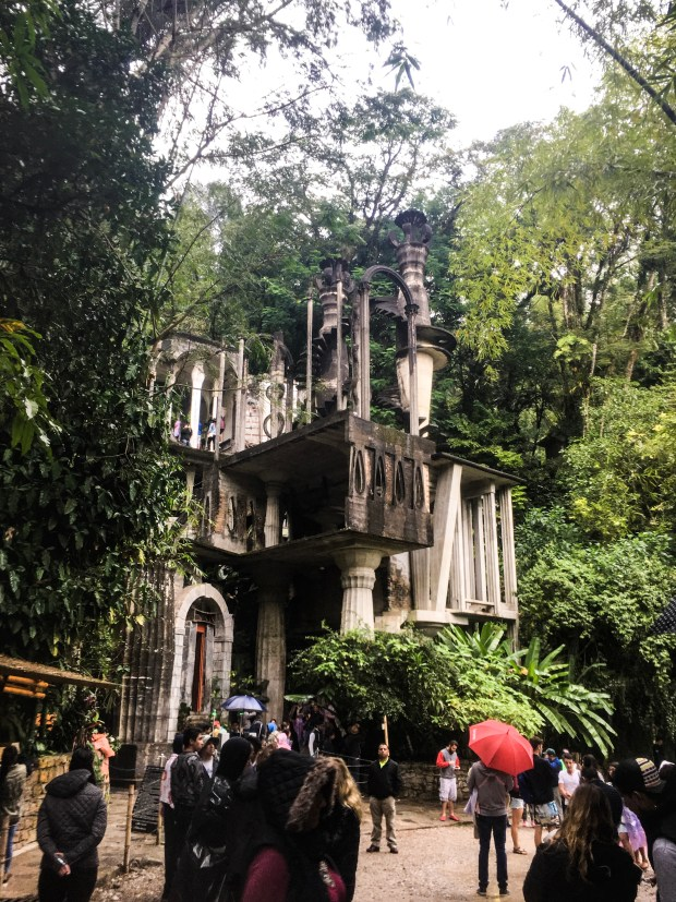 At the entrance to Las Pozas, there is what looks like a slightly gothic, unfinished building structure. It's white and gray, built from cement.