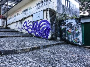 "Wide stone ""stairs"", with artwork on the wall in the background. It is a large, purple octopus."