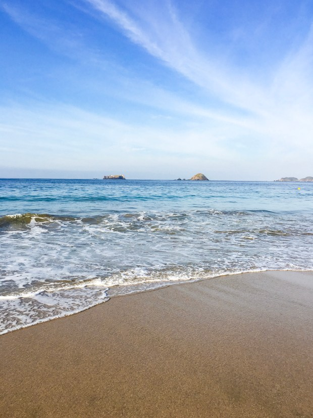 An ocean view from Ixtapa; the wave rolls in on the sand in the foreground. In the background, it's several shades of blue and in the horizeon, you see large rocks poking out. They aren't quite islands, though, merely large rocks.