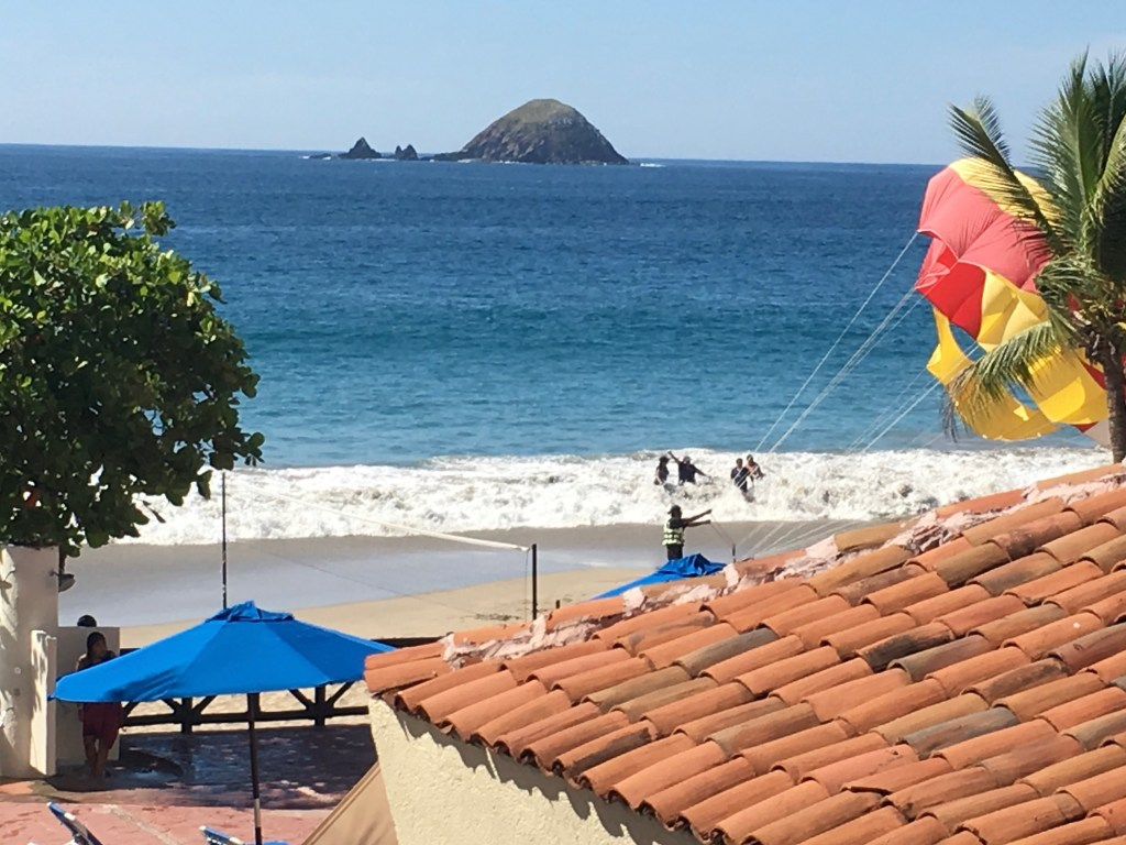 """The view from my blacony. There is a roof in the right foreground and a red and yellow parachute """"deflating"""" in the right mid ground. The beach and ocean are in the background."""