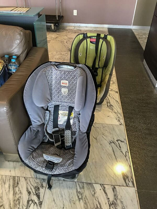 Two car seats sit on the ground in a hotel room. Are these the best travel car seats? Read on!