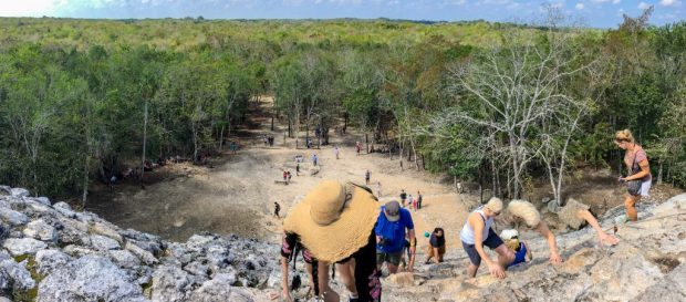 Panoramic view from the top of the Coba pyramid. You can see climbers climbing up in the foreground, the cleared part directly in front of the pyramid, and the green treeline in the background.